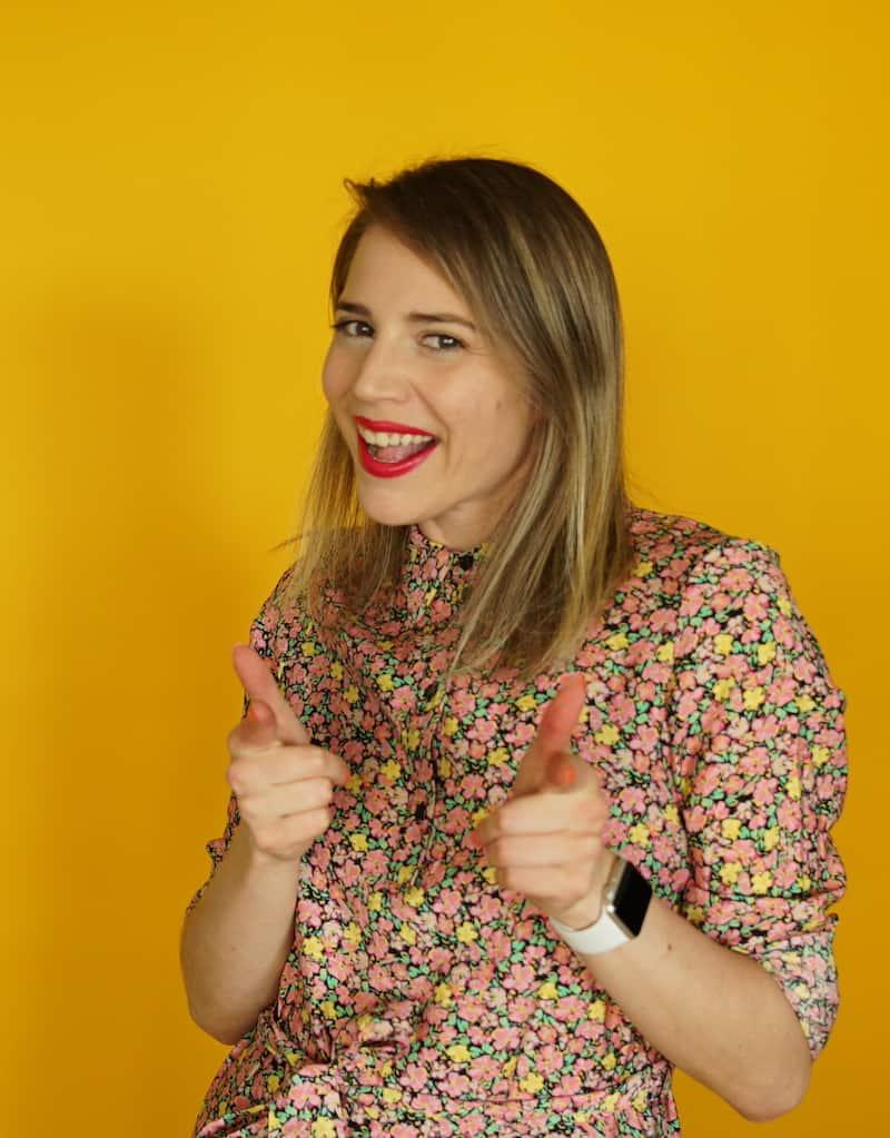 Emily Milling doing Finger Guns on Yellow Background